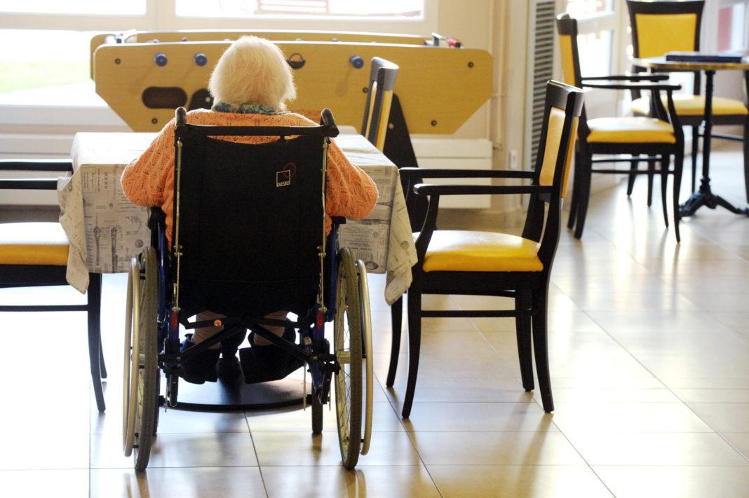 Personne âgée dans un fauteuil roulant dans une maison de retraite ; @Tesson/andia